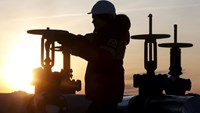 A worker checks the valve of an oil pipe at the Lukoil company owned Imilorskoye oil field outside the West Siberian city of Kogalym, Russia, January 25, 2016. REUTERS/Sergei Karpukhin
