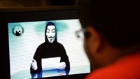 A man watches a video uploaded on the YouTube website of a person in a Guy Fawkes mask threatening to bring down Singapore's infrastructure to protest Internet regulations. Roslan Rahman/AFP via Getty Images