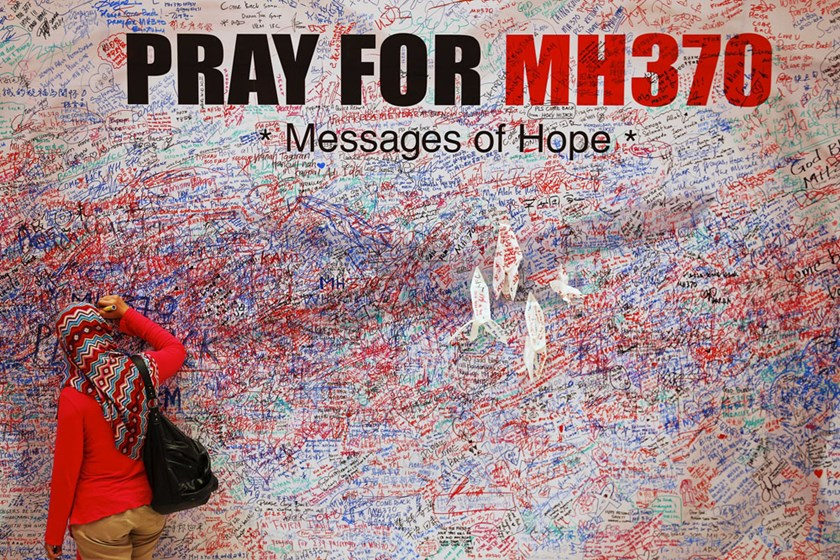 A woman leaves a message of support and hope for the passengers of the missing Malaysia Airlines MH370 in central Kuala Lumpur in this March 16, 2014 file photo.  Reuters/Damir Sagolj/Files