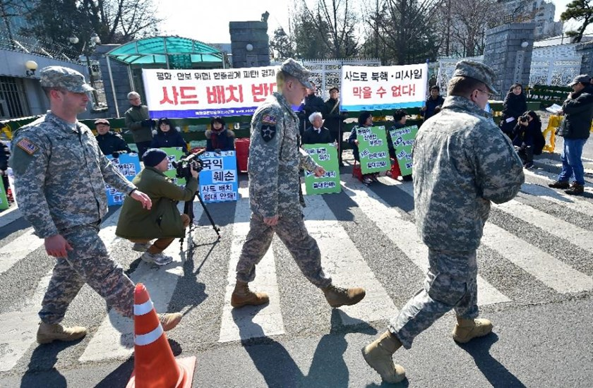 US soldiers walk past South Korean anti-war activists holding a rally against talks on deploying the Terminal High Altitude Area Defence System outside the Defense Ministry in Seoul on February 23, 2016. AFP/Jung Yeon-Je