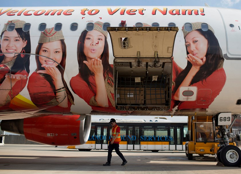 An employee walks under a Vietjet aircraft at Noi Bai International Airport in Hanoi. Photo: Bloomberg/Brent Lewin