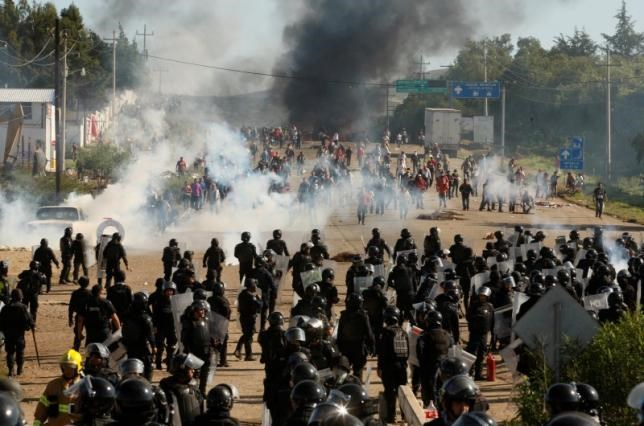 Protesters from the National Coordination of Education Workers (CNTE) teachers' union clash with riot police officers during a protest against President Enrique Pena Nieto's education reform, in the town of Nochixtlan, northwest of the state capital, Oaxaca City, Mexico on June 19, 2016. Photo: Reuters/Jorge Luis Plata