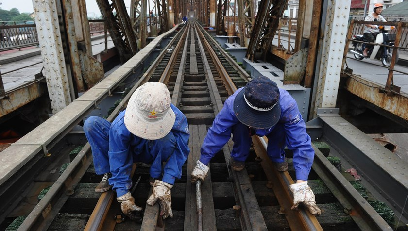 Railway workers do maintenance work on rail tracks on Long Bien Bridge in Hanoi. Vietnamese lawmakers have disagreed with the government on the latter's recommendation for raising retirement age. Photo credit: AFP