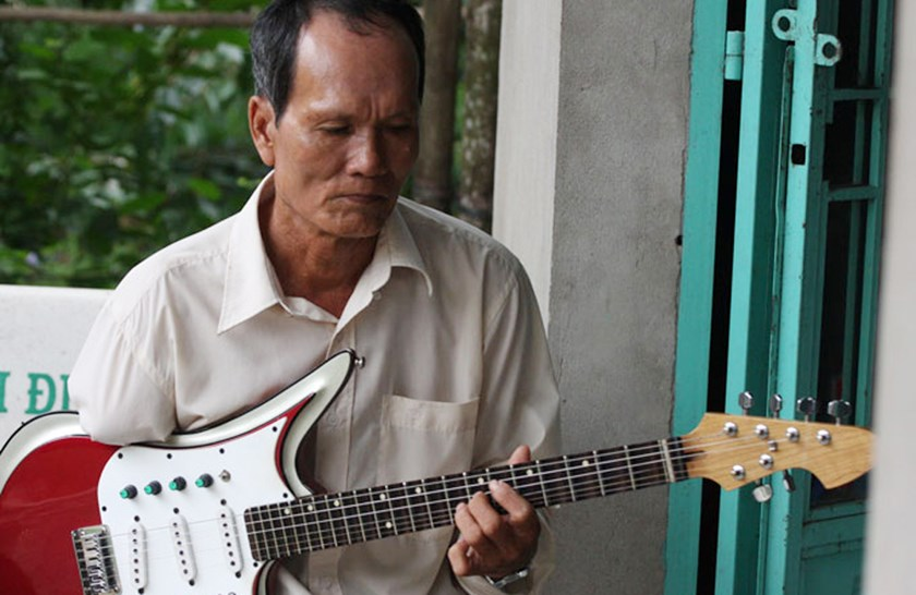 Thai Van Hai, 65, plays guitar with his left hand only. Photo credit: Tuoi Tre