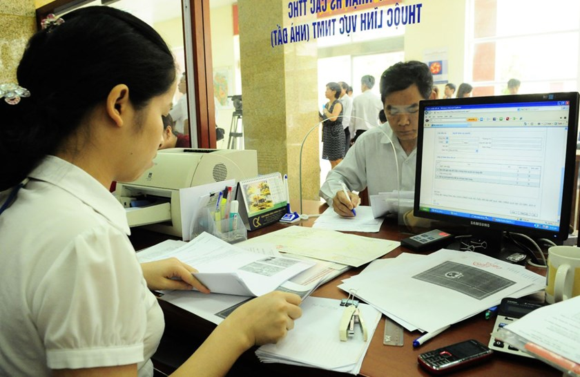 A public servant (L) works with landing papers at a state agency. File photo