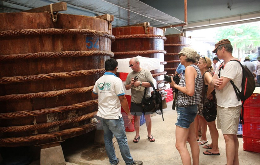Foreign tourists visit a fish sauce making plant in Phu Quoc. Photo: VNA