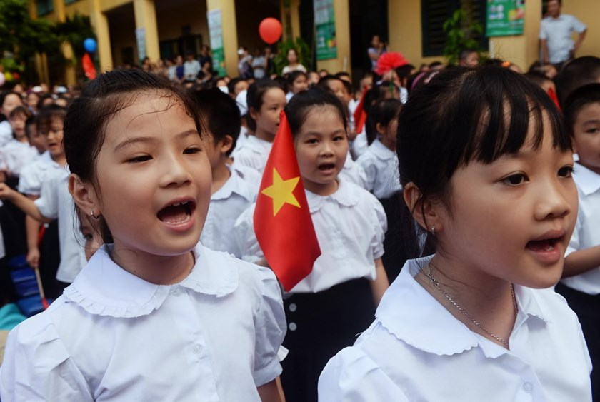 Students sing the national during a ceremony marking the new school year at a local elementary school in Hanoi. Photo: AFP
