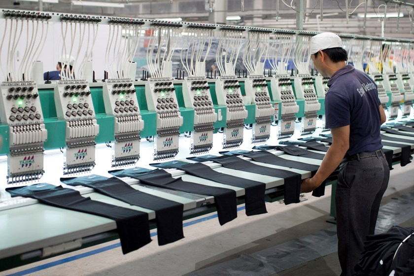 A worker arranges pieces of fabric under embroidery machines inside a foreign-owned garment factory in the southern province of Binh Duong. Photo: Bloomberg