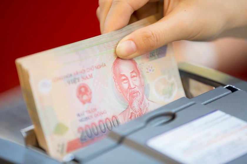 An employee places Vietnamese dong banknotes in a money-counting machine for an arranged photograph inside a Ho Chi Minh City Housing Development Commercial Joint-Stock Bank (HDBank) branch in Ho Chi Minh City. Photo: Bloomberg