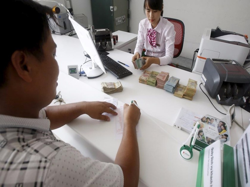 A bank employee (R) counts Vietnamese dong banknotes at a bank in the northern province of Vinh Phuc. Photo: Reuters