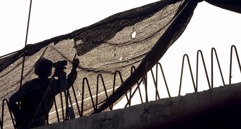 A laborer of a state-owned bridge building company works at a construction site of a bridge in Hanoi. Photo: Reuters
