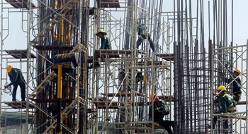 Workers arrange steel structures at a construction site of an office building in Hanoi. Photo: Reuters