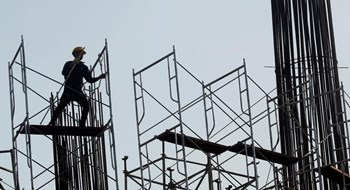 A worker arranges steel structures at a construction site of an office building in Hanoi. Photo: Reuters