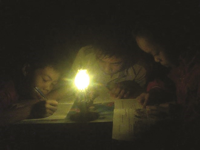 "Children study with a kerosene lamp in ""oil lamp village"" in the northern province of Hoa Binh. Photo: Tran Ho"