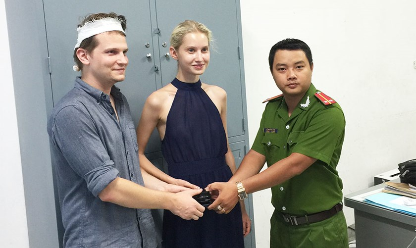 German Sebastian Gertz and his Kazakh girlfriend Yekaterina Ponomarenko receive their belongings from a police officer in Ho Chi Minh City's District 1 on October 28, 2015. Photo: Ngoc Tho