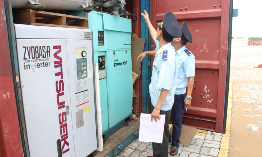 Customs officers check a container of used machinery at a seaport in Ho Chi Minh City. Photo: Ngoc Tho