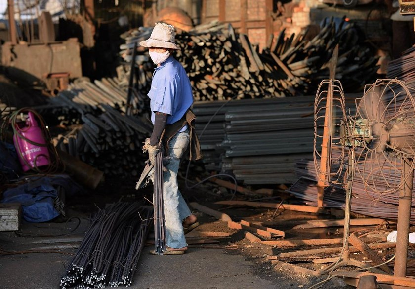 A worker works at a private steel workshop which produces steel rods for construction from scrap iron in Dong Anh District on the outskirts of Hanoi. Photo: AFP