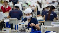 Workers sew clothing with sewing machines at a foreign-owned garment factory in the southern province of Binh Duong. Photo: Bloomberg