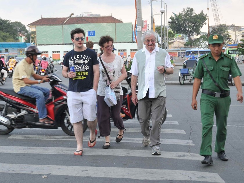 Foreign tourists cross a street in Ho Chi Minh City. Photo: Diep Duc Minh