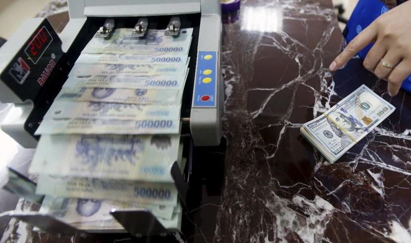 An employee counts Vietnamese dong bank-notes near U.S. dollar bank-notes at a bank in Hanoi. Photo: Reuters