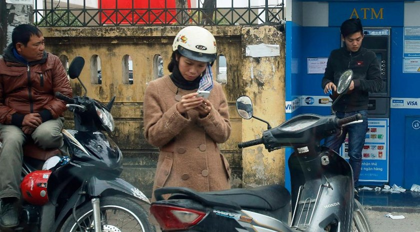 A woman types on a mobile phone on a street in Hanoi. Photo: Reuters
