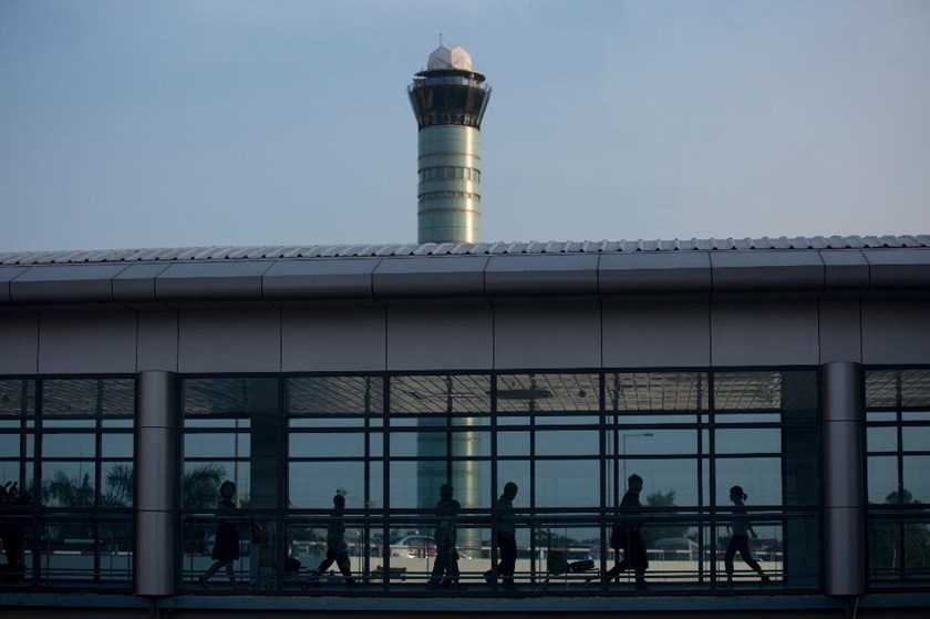 An air traffic control tower stands behind a walkway at Noi Bai International Airport in Hanoi. Photo: Bloomberg