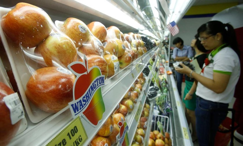 A woman checks the price of fruit at a supermarket in Hanoi. Photo: Reuters