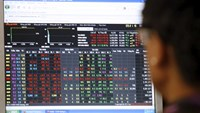 An investor looks at a stock market screen at a securities company. Photo: Reuters