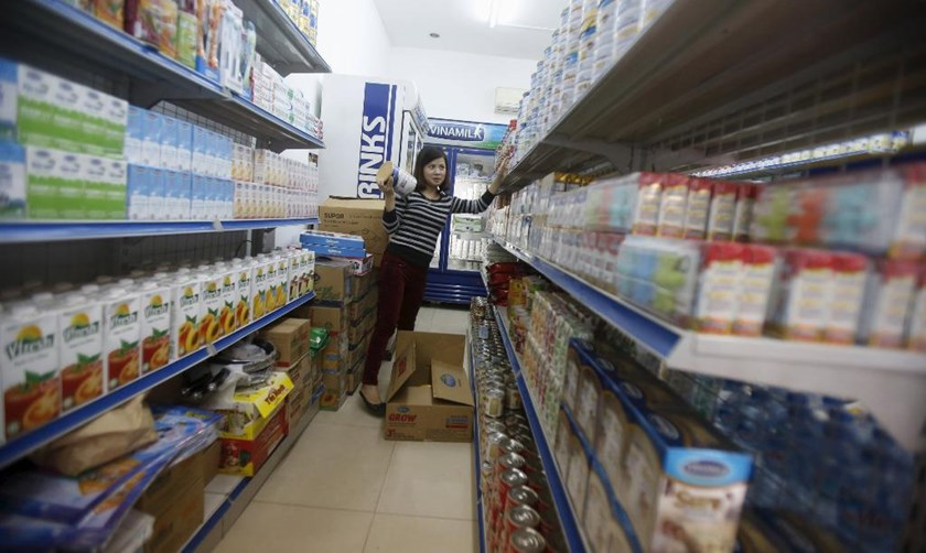 An employee loads products on to shelves at a Vinamilk's shop in Hanoi. Photo: Reuters