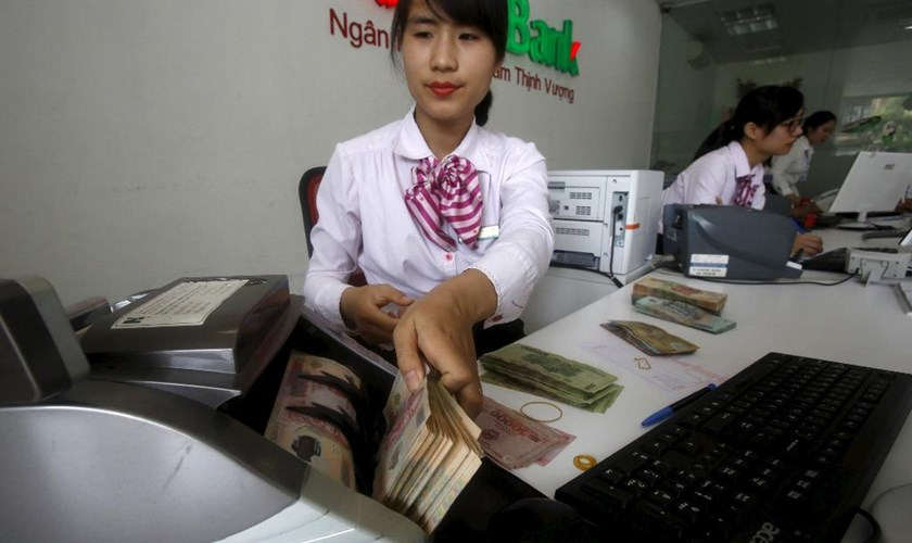 A bank employee counts Vietnamese dong bills at a bank in Vietnam. Photo: Reuters