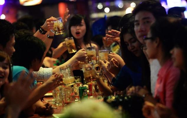 People enjoy drinks at an open-air beer bar in downtown Ho Chi Minh City. Photo: AFP