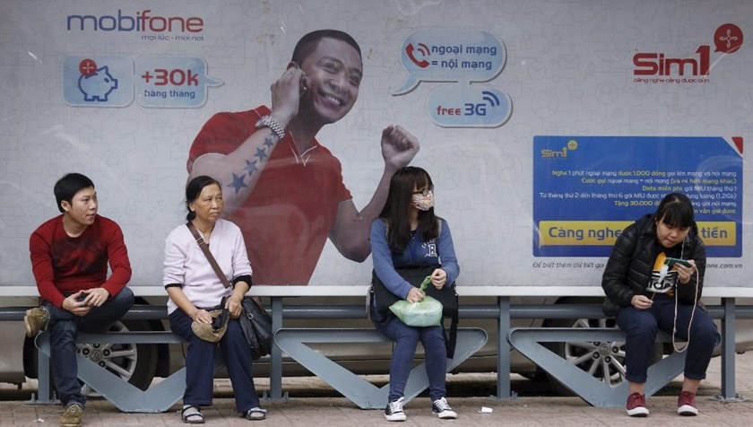People waiting for a bus in front of an advertising billboard of Mobifone in Hanoi. Photo: Reuters