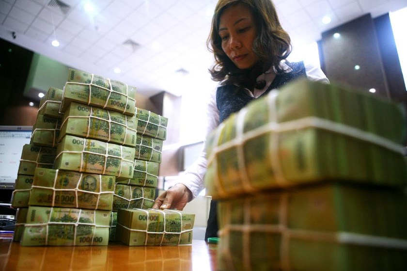 A staff member arranges stacks of money at a bank in Hanoi. Photo: Ngoc Thang