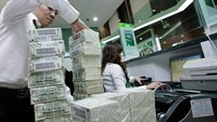 An employee arranges stacks of dollar notes at a bank in Vietnam. Photo: Ngoc Thang
