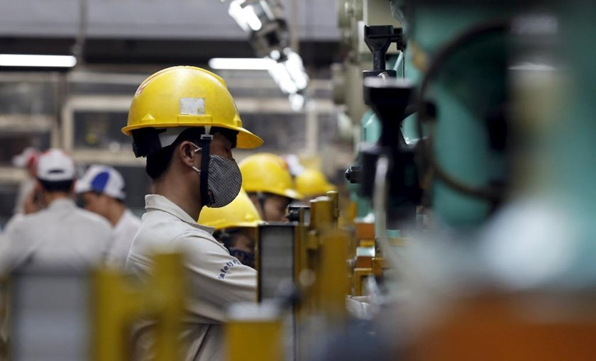 Laborers work at a foreign-owned company which produces car and motorcycle parts outside Hanoi. Photo: Reuters