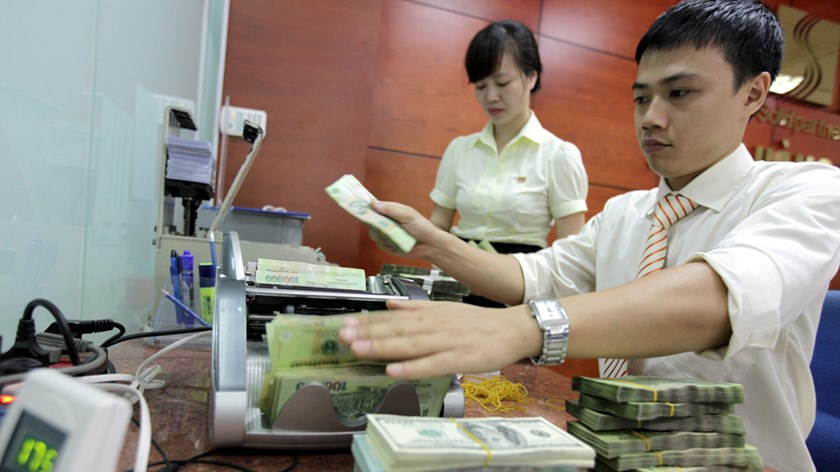 An undated photo of an employee counting notes at a bank in Hanoi. Photo: Ngoc Thang