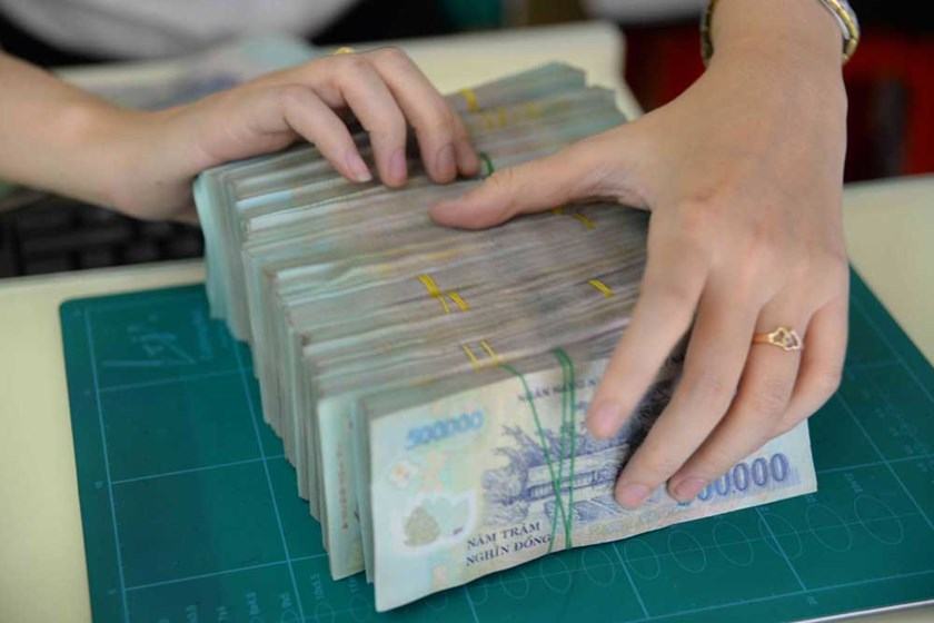 An employee arranges dong bills at a bank in Ho Chi Minh City. Photo: Diep Duc Minh/Thanh Nien