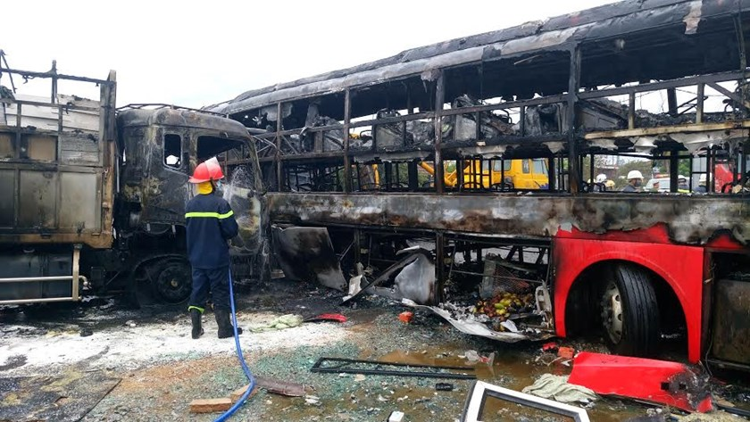 A bus is burned down and a truck is partly destroyed in a multiple-vehicle collision that left at least 12 people dead in the central province of Binh Thuan in the early morning on May 22, 2016. Photo: Que Ha