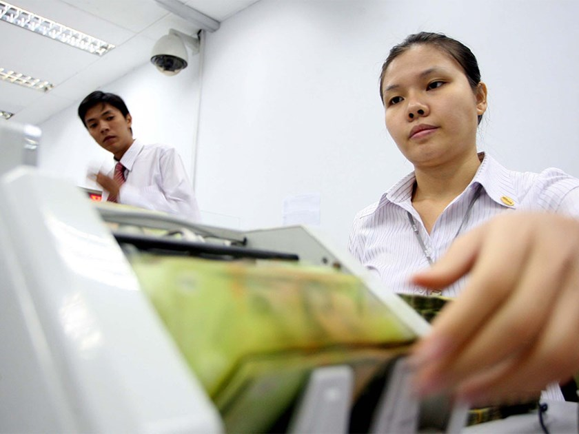 A file photo of staff counting notes at a bank in Hanoi. Photo: Ngoc Thang