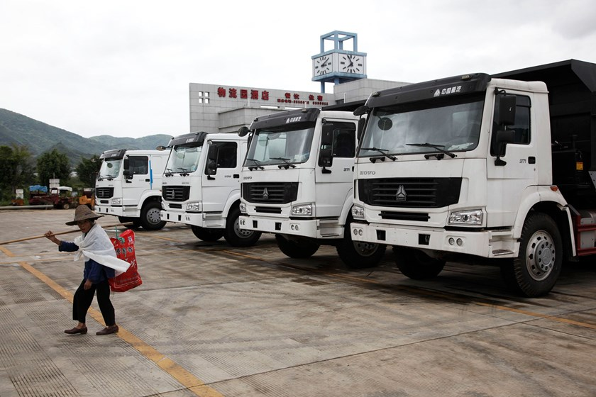 A woman walks past a line of heavy duty trucks waiting to be exported into Vietnam at a China-ASEAN free trade zone logistics center near the city of Pingxiang in Guangxi Province, China in this 2009 file photo. Photo credit: Bloomberg