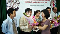 Ho Thi Y Nhi, financial director of East Meets West offers flowers to its partners in four central localities and a representative of the Da Nang University of Medical Technology and Pharmacy on June 9, 2014. Photo credit: EMW