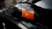 A Vietnamese flag is displayed on a car's wing mirror in Hanoi, Vietnam, on May 30, 2014. Photo credit: Bloomberg