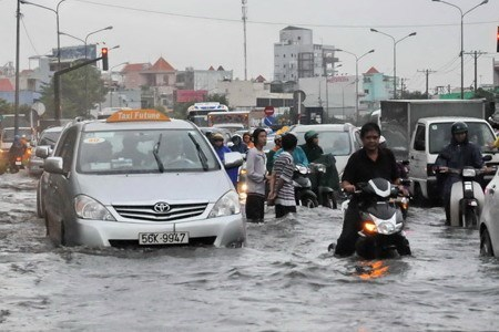 Vehicles struggle through a flooded road after downpours in Ho Chi Minh City in 2010. Photo by Dinh Phu