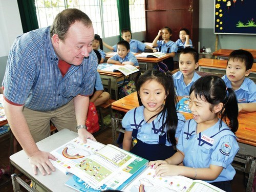 A foreign teacher teaches English at an elementary school in Ho Chi Minh City. Up to 52 percent of expats in Vietnam said they earn more than they would have at home. Photo: Dao Ngoc Thach