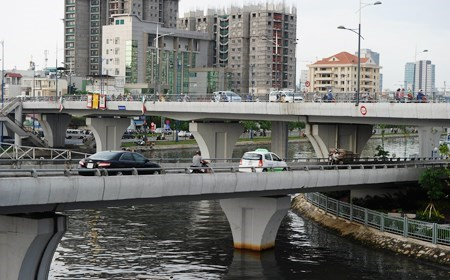 Cars and motorcyclists on a bridge built over the Saigon River in Ho Chi Minh City. Public debts will be used only for important and essential infrastructure and socioeconomic projects (Photo: AFP)