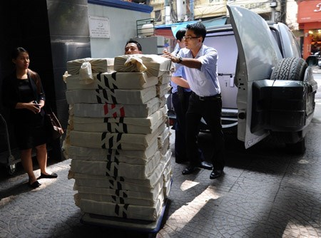 Bank employees delivering currency in Hanoi. Photo: AFP