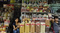 Women sit at a store selling coffee and snacks at Ben Thanh market in Ho Chi Minh City, Vietnam.