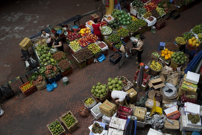 Vendors sell produce at the Cho Hom market in Hanoi. Photo credit: Bloomberg
