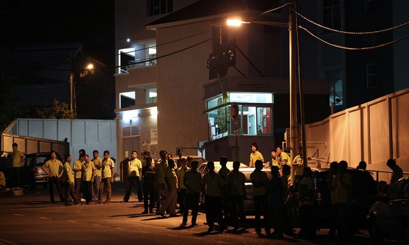 Factory workers wait for rides at dawn in the neighborhood of Majestic Heights in Paya Terubong, Penang, Malaysia in 2013. Photo: Bloomberg