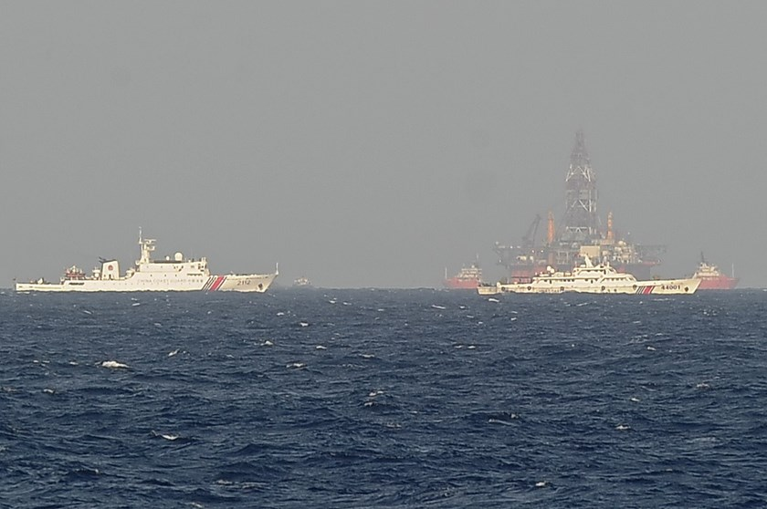 This picture taken on May 14, 2014 from a Vietnamese coast guard ship shows Chinese coast guard vessels sailing near China's oil drilling rig in Vietnam's territorial waters in the East Sea, internationally known as the South China Sea.  Photo credit: AFP